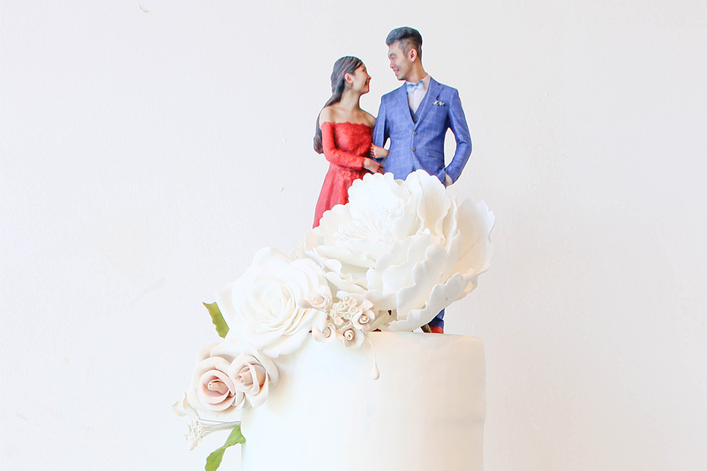 3D statuette of a newly married couple placed on a wedding cake.